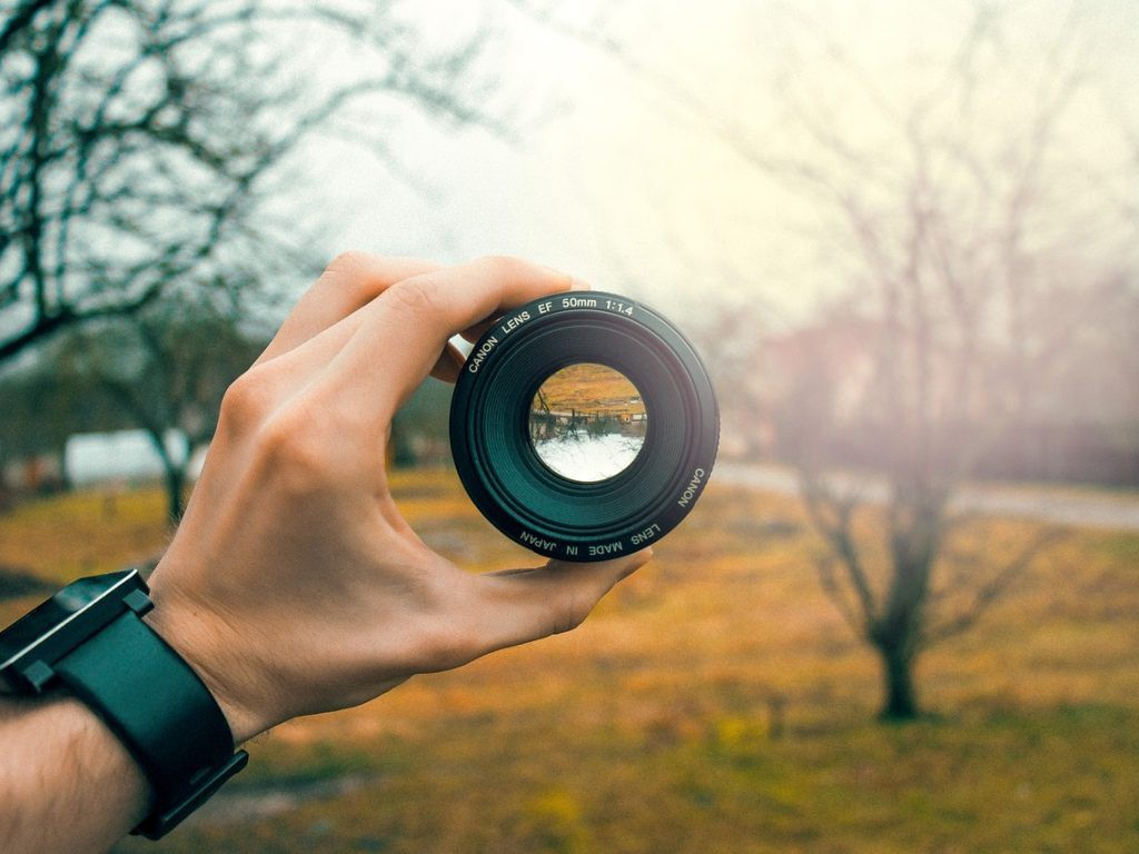 Lente de cámara Canon tomada por un hombre dentro de un bosque